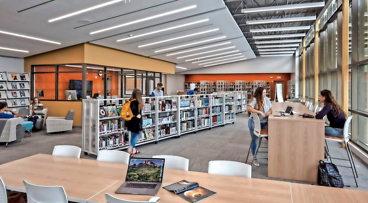A rendering of a high school library designed by CSArch that includes mobile book stacks, high-top seating and a media center.