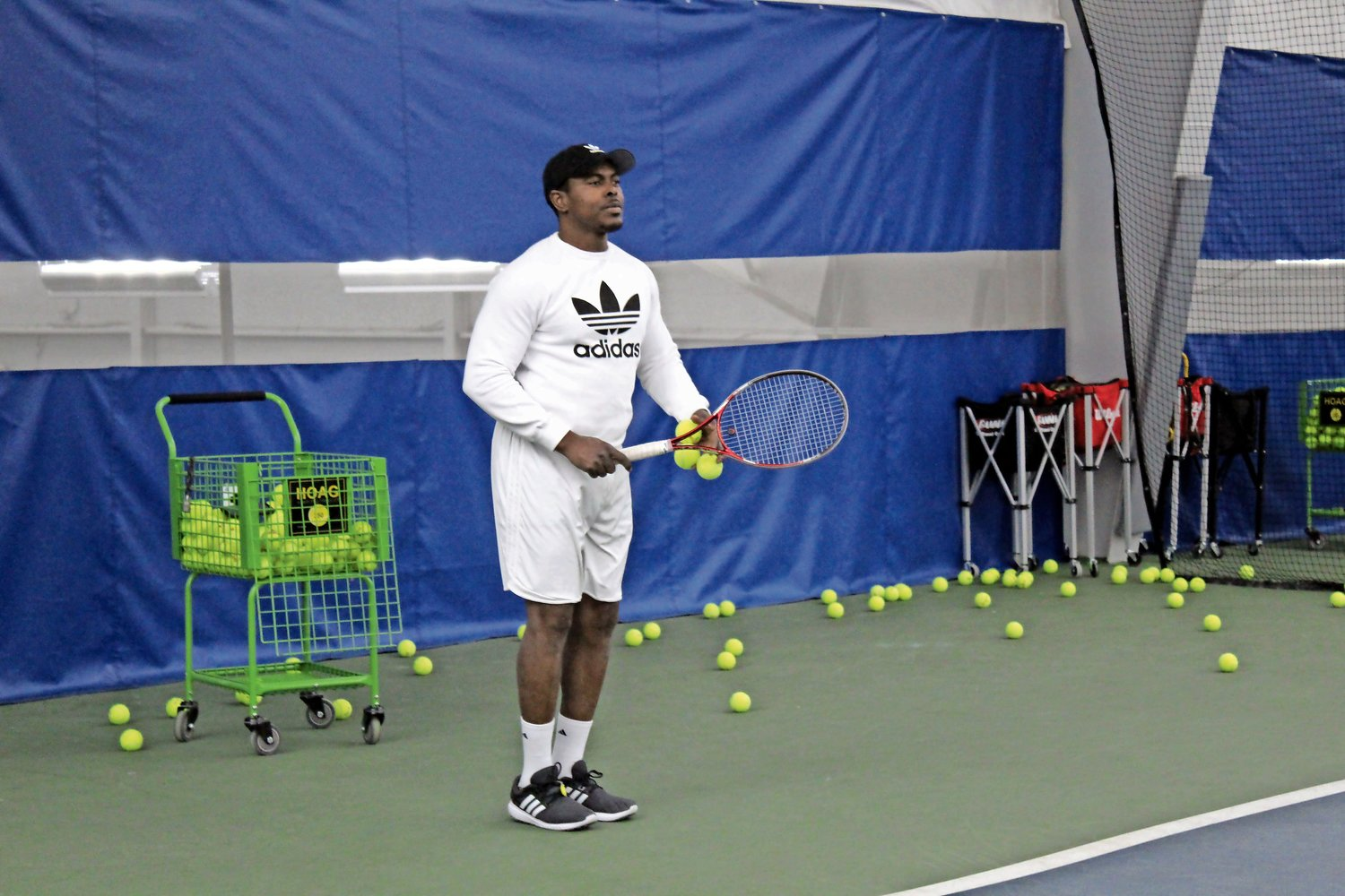 Instructor Gary Harrison, from Jamaica, prepared to launch serves to his client at the Glen Head Racquet Club.