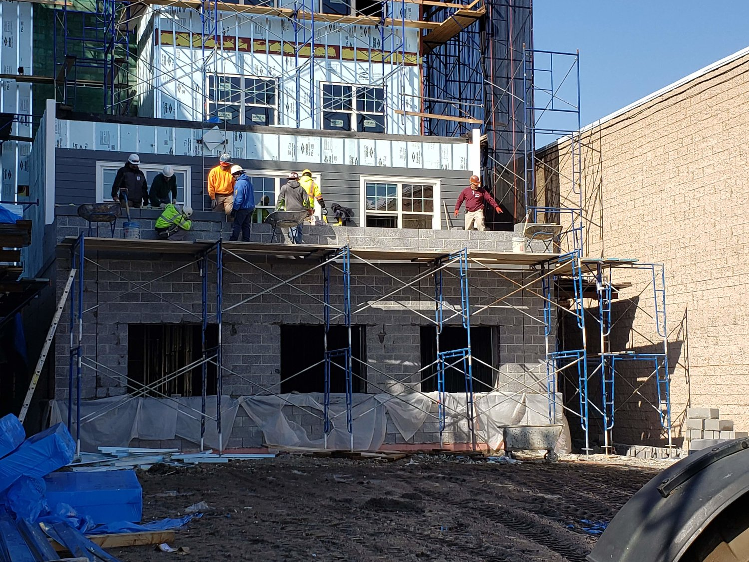 Construction workers were seen working on the new apartment building's exterior.