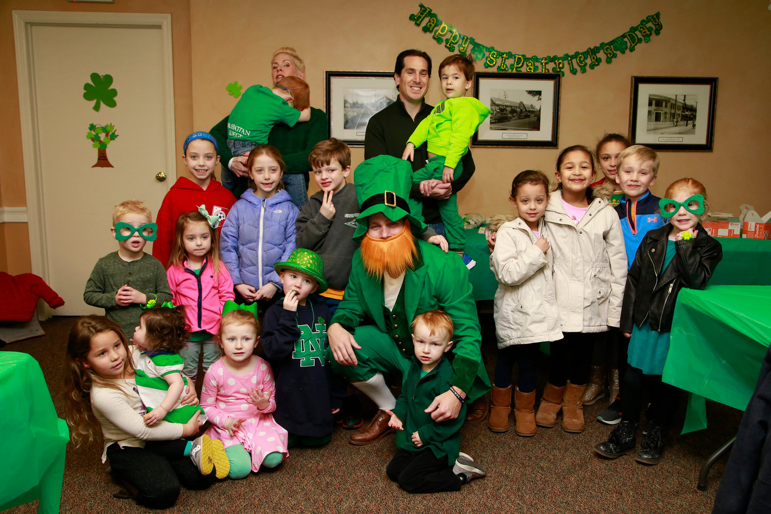 Parents and children posed with the Leprechaun during Malverne Youth Board's St. Patrick's Day Party.