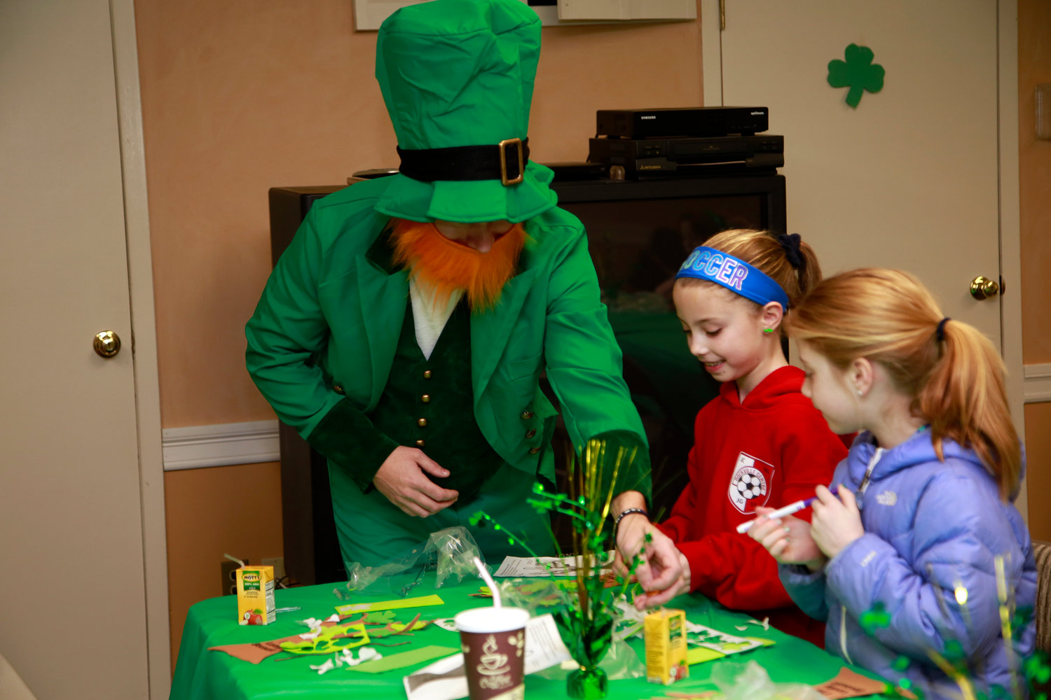 Shamus the Leprechaun gave coins to the Rick sisters, Bernadette, 9, center, and Caroline, 7.