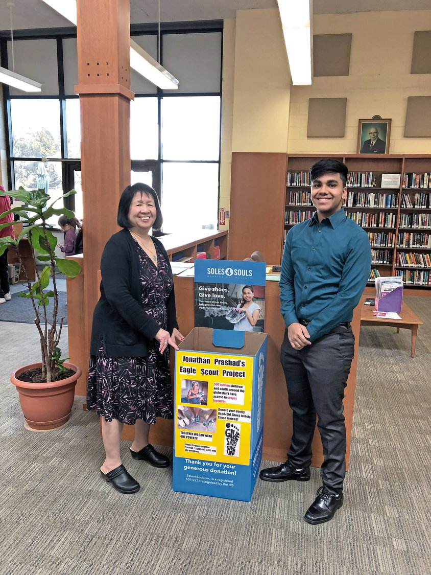 Jonathan Prashad, right, set up a Soles4Souls donation box at the Henry Waldinger Memorial Library. He is with Library Director Mamie Eng.