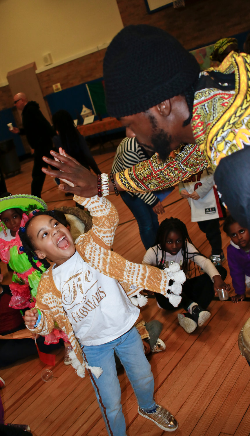 African drum performer Daniel Jones, right, representing the Republic of Guinea, got a happy high five from kindergartener Alyssa Jean after his performance. Alyssa and her family represented Barbados at the event.