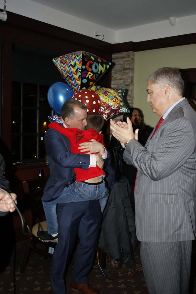 New Board of trustees member Chris Squeri's son, Hudson, hugged his father shortly after the election results, while Jorge Martinez looked on.