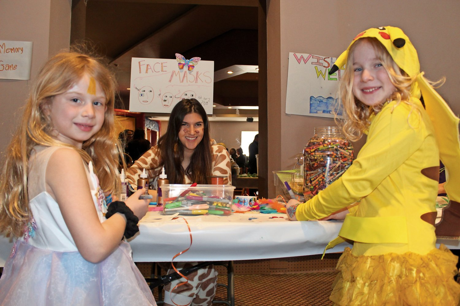 Julia Stroot, left, and Eliana Ecker, right, got some help making Purim masks from teen volunteer Gaby Brichta.