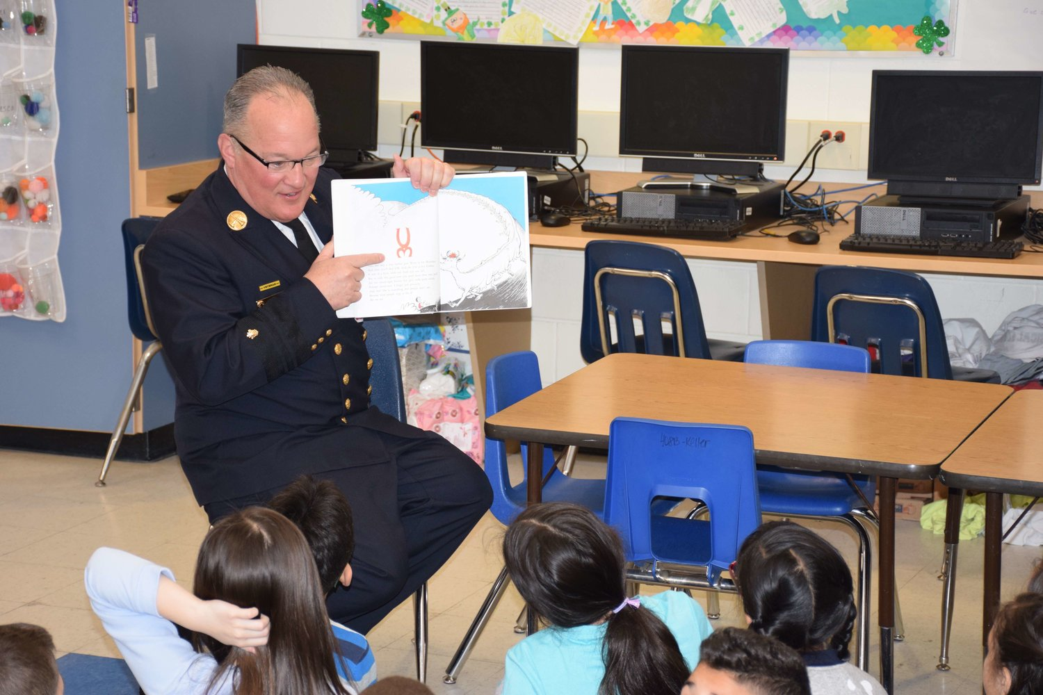Paul Kosiba, the third assistant chief of the East Meadow Fire Department, read to a class at Bowling Green Elementary School on March 8 as part of its Pick a Reading Partner program.
