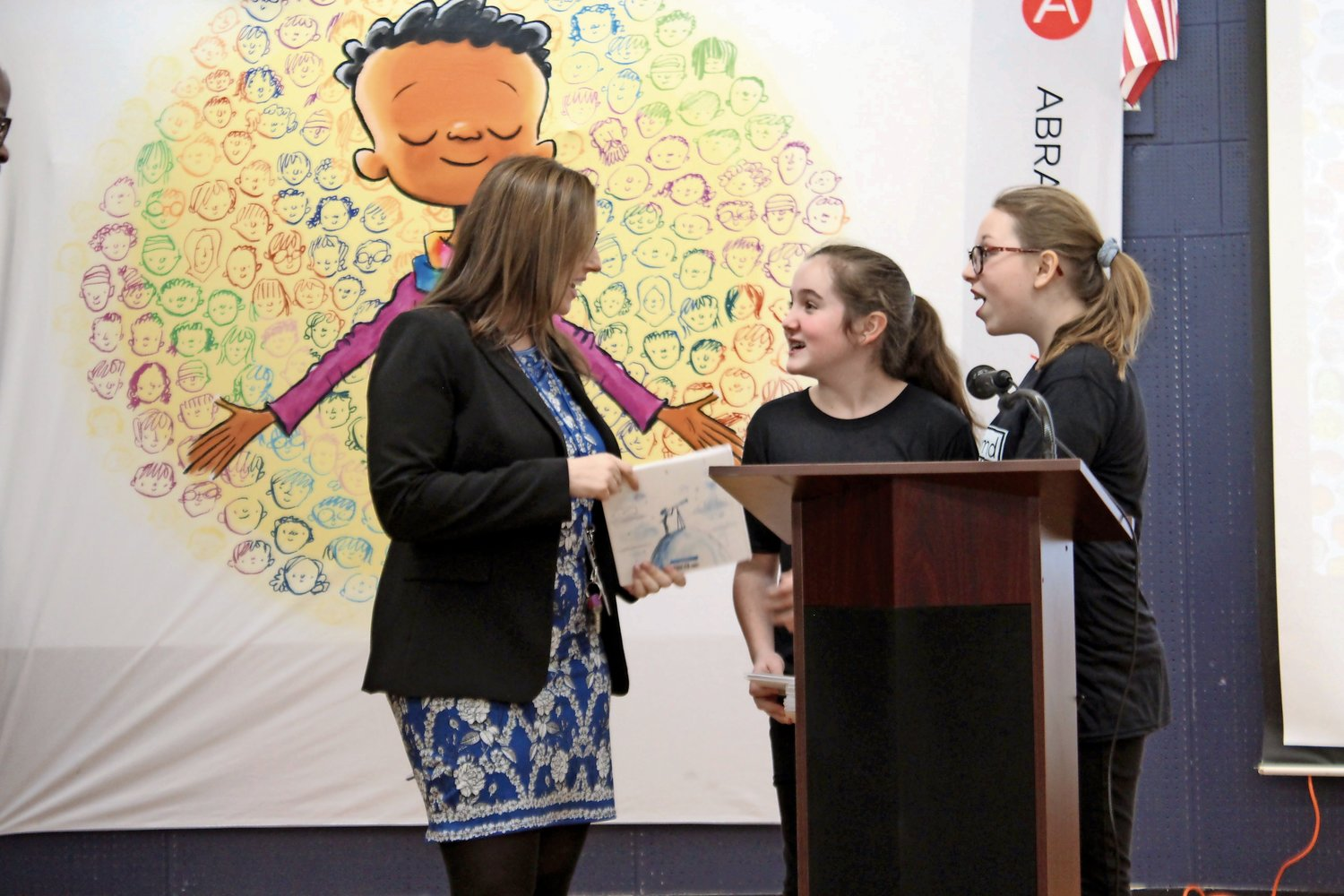 "The morning's masters of ceremonies, Project EXTRA students Riley Rugolo and Reese Allegra, gave a copy of ""I Am Human"" for the School No. 2 library to Principal Erin Marone. Books were donated to all schools in the district, as well as the Oceanside Public Library."