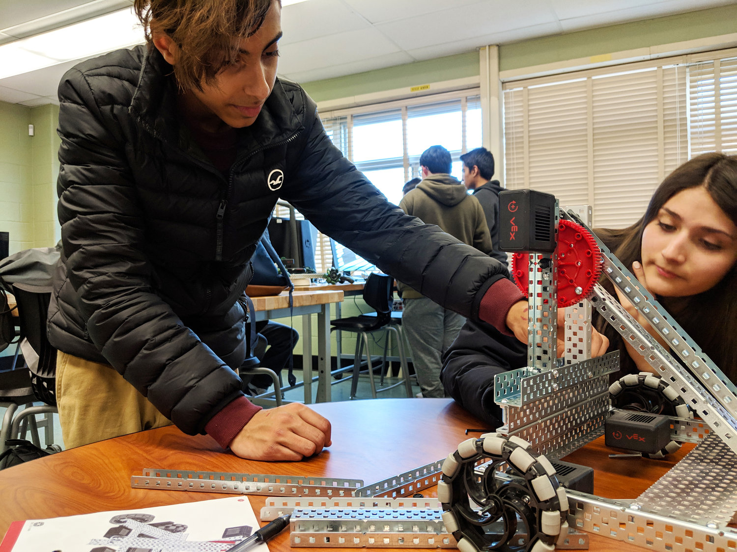 Sophomore Connor Gibson tinkered with his group's second catapult-robot while his teammate Missel Khen looked on.