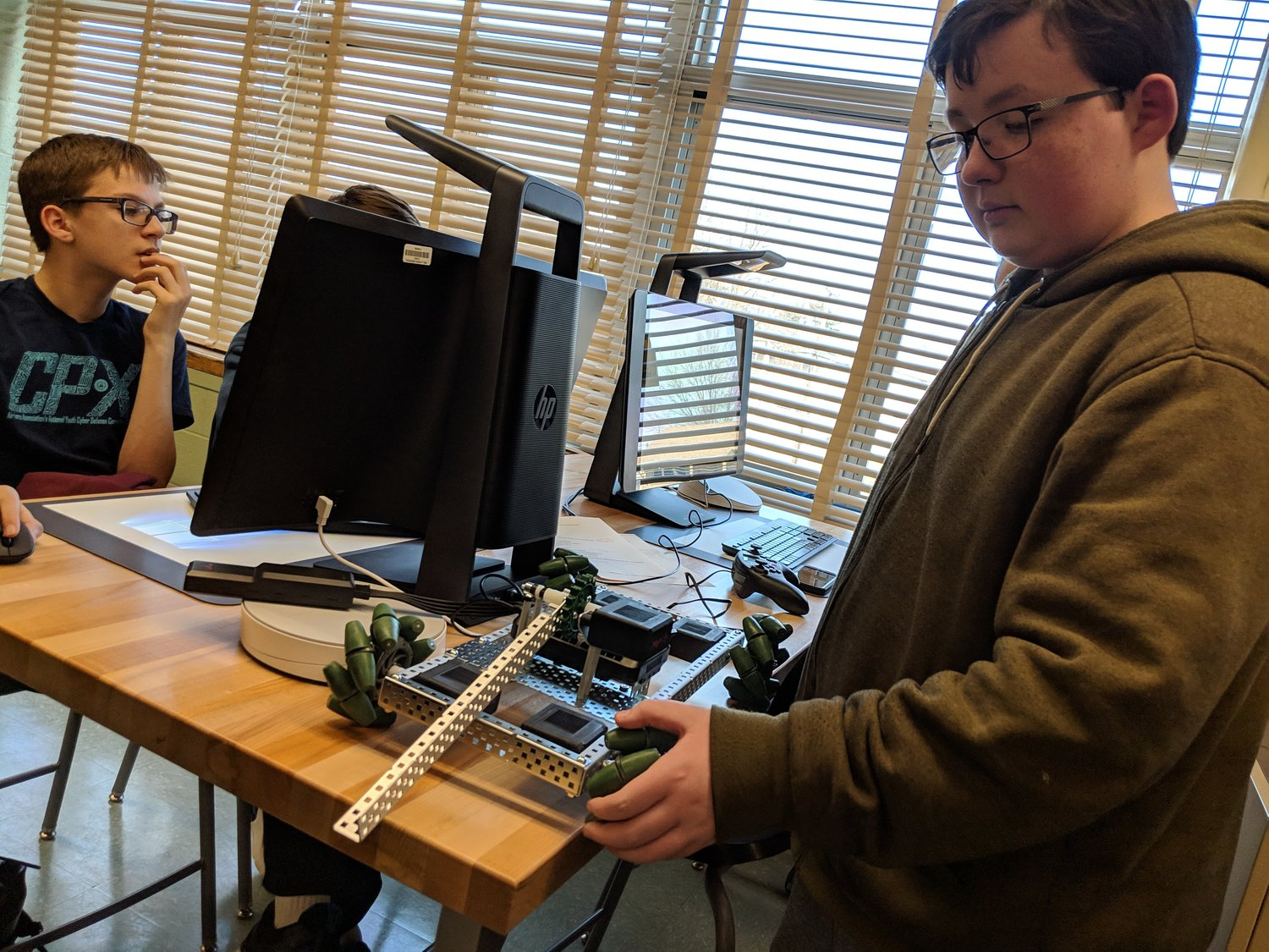 "Junior Ross Seifer explained the unique treads on his team's robot while a teammate tried to fix the machine's coding. ""The treads are so it can move in any direction,"" he said. ""It can go from side to side."""