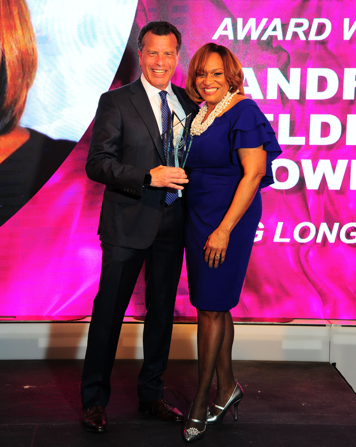 Stuart Richner presented an award to Andrea Elder-Howell, vice president of legal at PSEG Long Island.