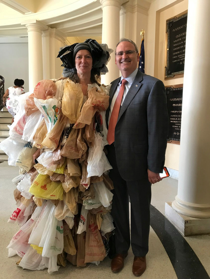 Lynbrook resident Susan Brockmann, above with Nassau County Legislator C. William Gaylor, stood outside the County Legislative Building in Mineola last May, wearing 500 plastic bags. She did so in protest of their use.