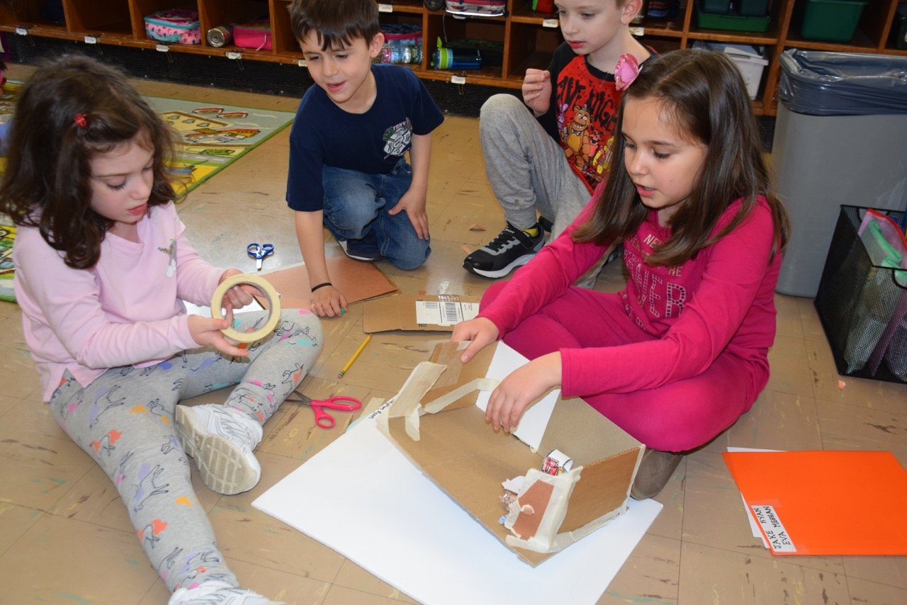 Kindergartners Meghan LeMieux, far left, and Ryan Hotine constructed a house for the Three Little Pigs with the guidance of second-graders Jake Vermillion and Eva Jaszczuk.