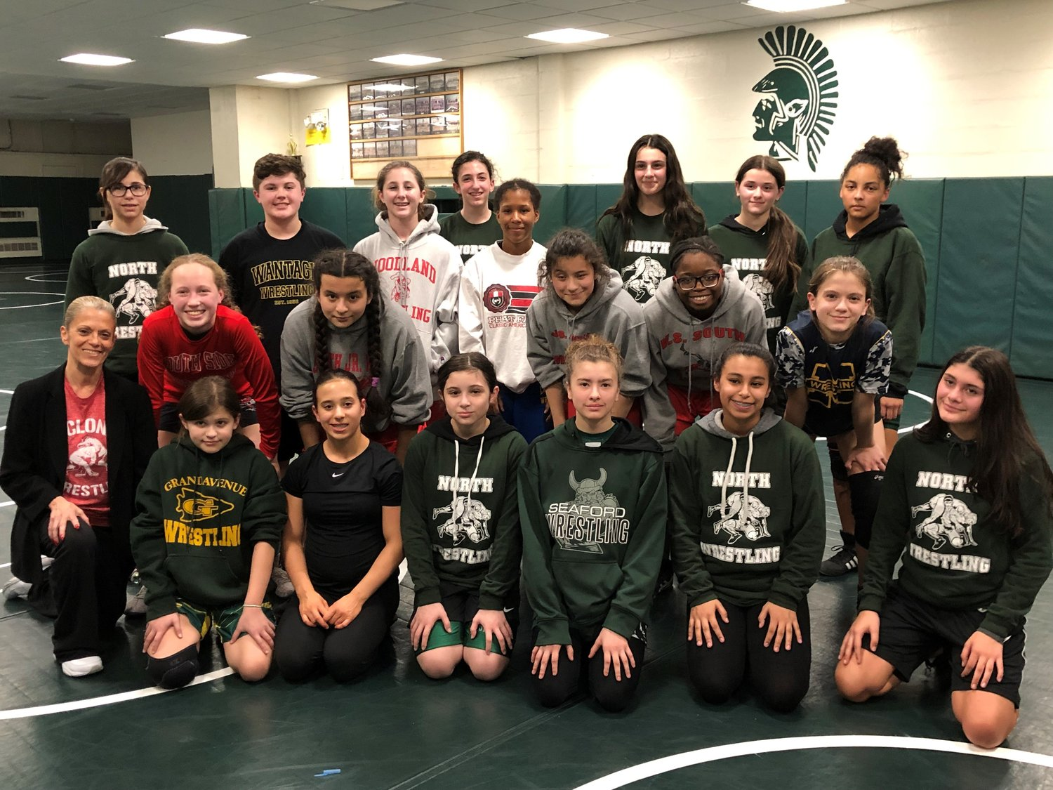 Nineteen girls, including South Side Middle School eighth-grader Mia Reisert, in red, competed in an all-girls wrestling event at Valley Stream North High School last month. Carol Roseto, the Rockville Centre School District's athletic director, left, joined them,