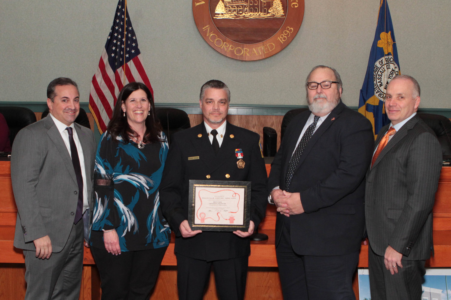 The village board honored Fire Chief Brian Cook, center, on April 1.