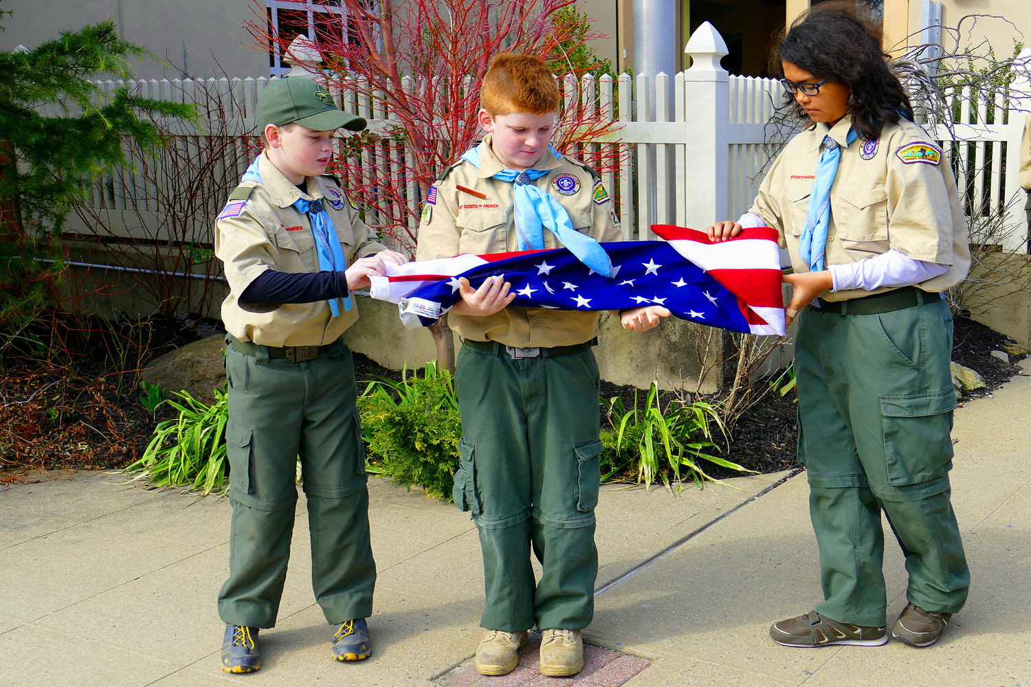 To open the festivities, Boy Scouts Max Einstman, far left, Alexander Krzeminski and Robert Schlageter unfurled an American flag and raised it.