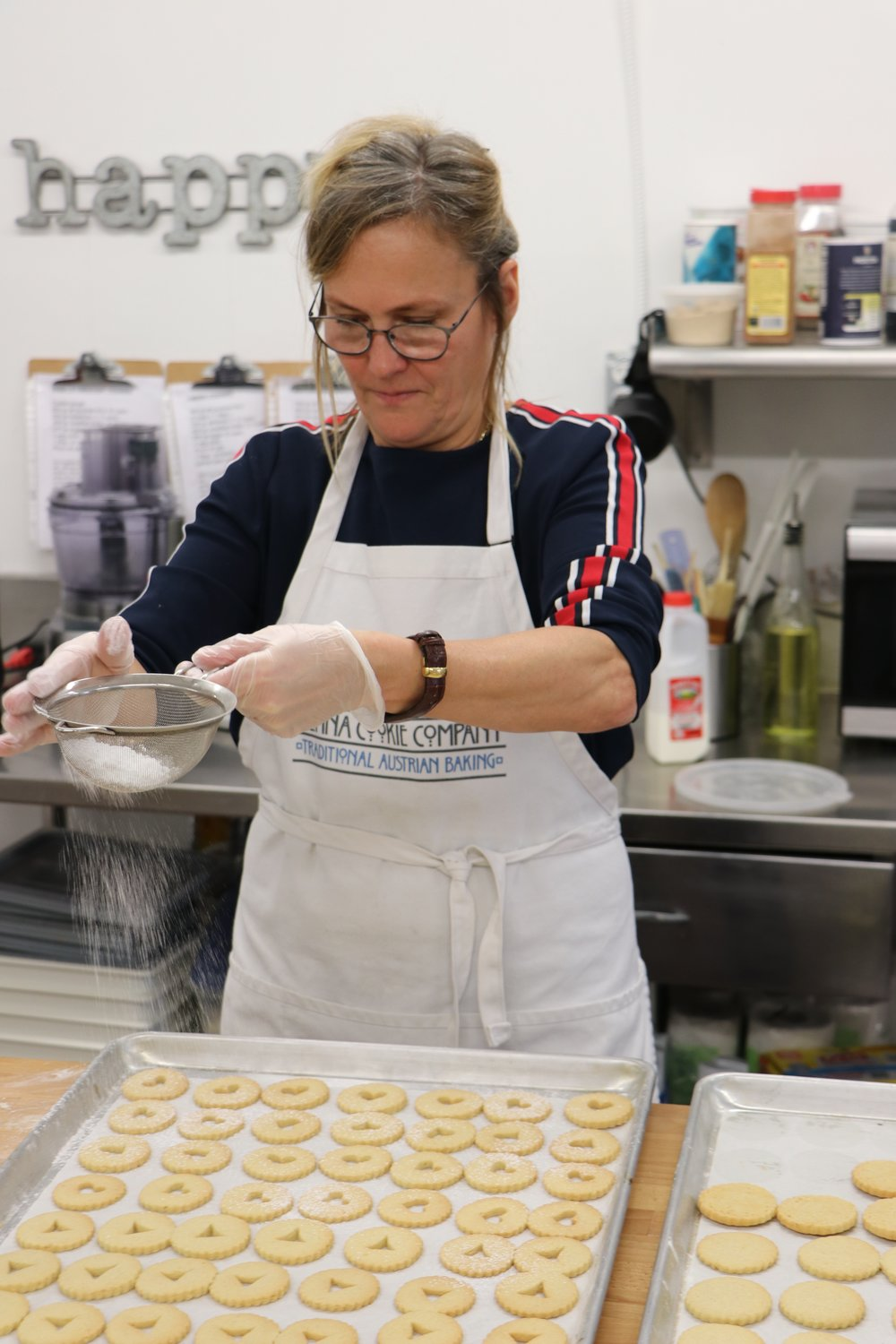 Heidi Riegler dusts a tray of Linzer cookies with powdered sugar before filling them with jam.