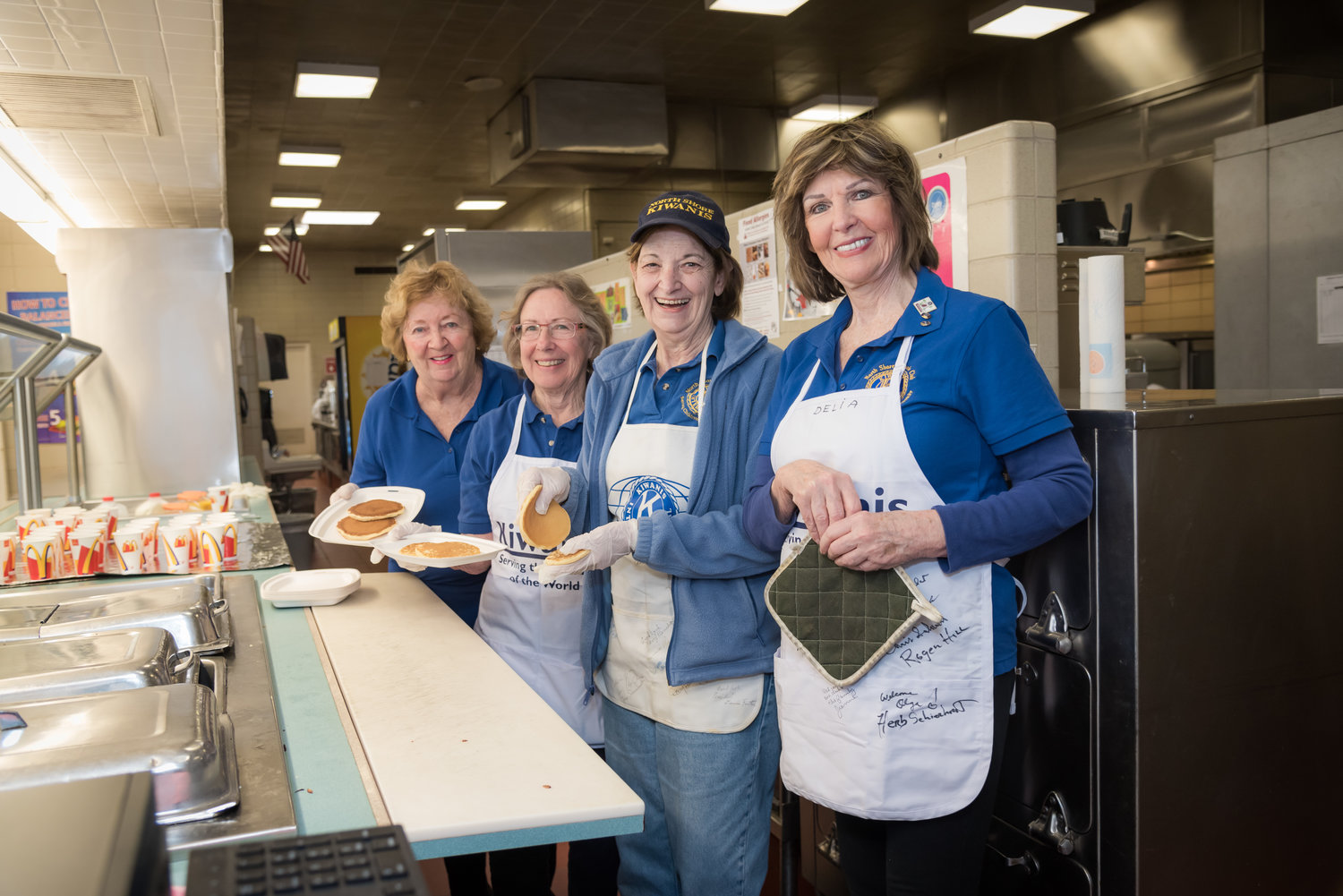Kiwanians Merle DeMott, far left, Sonja Nelson, Meredith Brosnan and Delia Verna worked behind the line to serve up steamy plates of fluffy pancakes to guests.