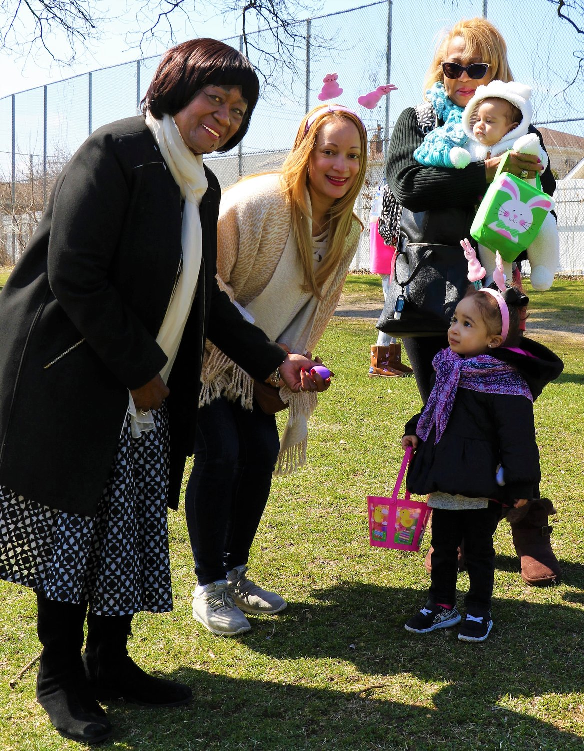 Starr Abreu, 2, received an Easter treat from Town Senior Councilwoman Dorothy Goosby, left,. Abreu's mother, Ruth Perez, and grandmother Noelia Paredes, holding Dylan Abreu, joined them.