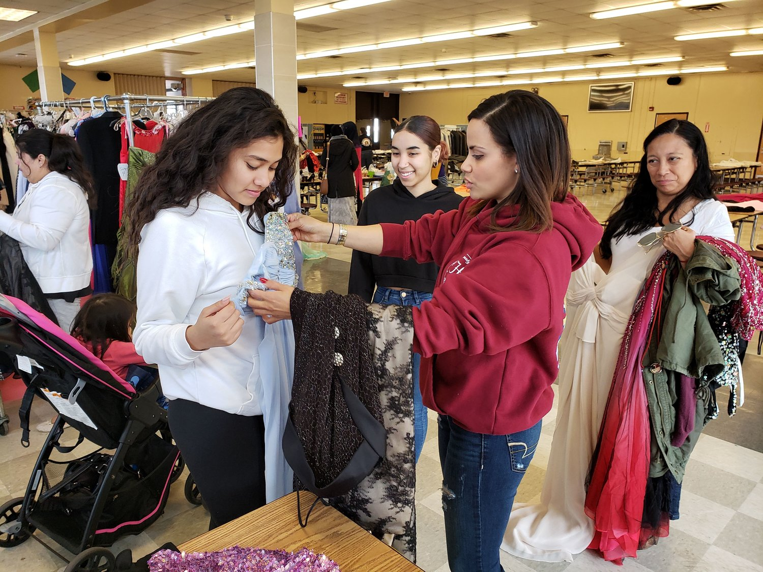 Freeport Police officer Samantha Sepulveda, right, helped Freeport High School senior Jylene Jaquez, 18, pick out a dress for the prom, while senior Valentina Vinusuion, 17, looked on at A Dream Prom Boutique on March 30.