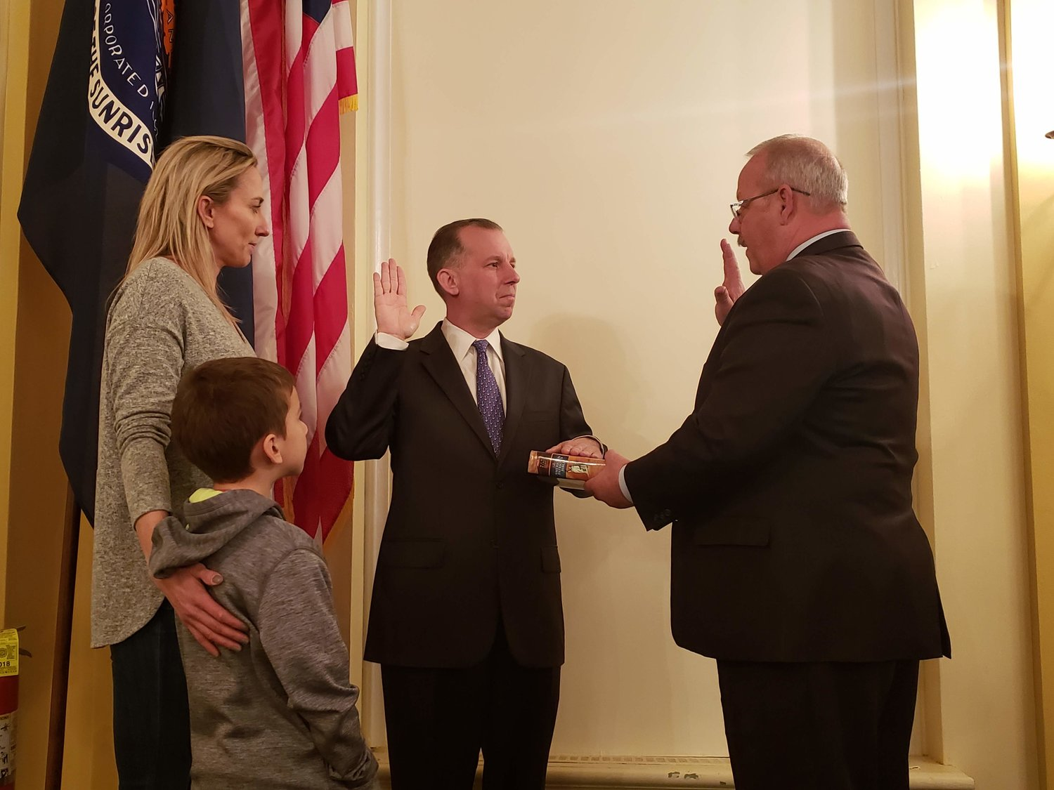 New village Trustee Chris Squeri was sworn in by Mayor Robert Kennedy on April 1. He was joined by his wife and son.