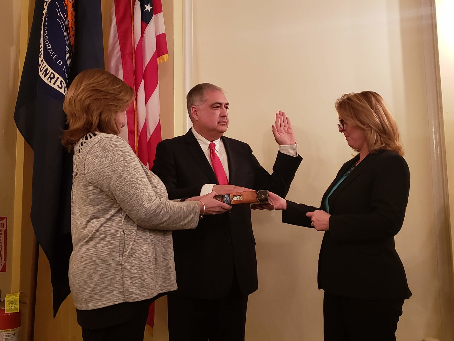 Deputy Mayor Jorge Martinez, joined by his wife, Christine, left, was sworn in by Nassau County Legislator Debra Mulé.