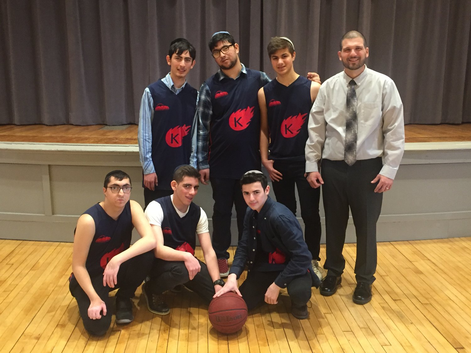 The Kulanu Academy 2019 boys' basketball team. Standing, from left, Moshe Levinson, Moshe Marashli, Yossi Tahalov and coach Vincent Rougê. Kneeling, from left, Gavriel Imani, Yosef Krasner and Donny Hoschander. Not pictured: Mayer Farah, Menachem Jacobs and Mike Khadeida.