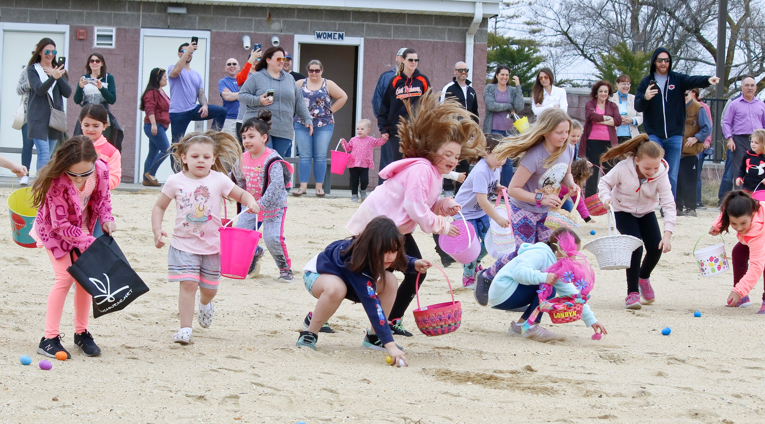 Nearly 200 children ran to grab the 2,000 eggs scattered along the beach front at the annual Hewlett Point Beach egg hunt hosted by the Cape Cod Homeowners' Association on April 14.