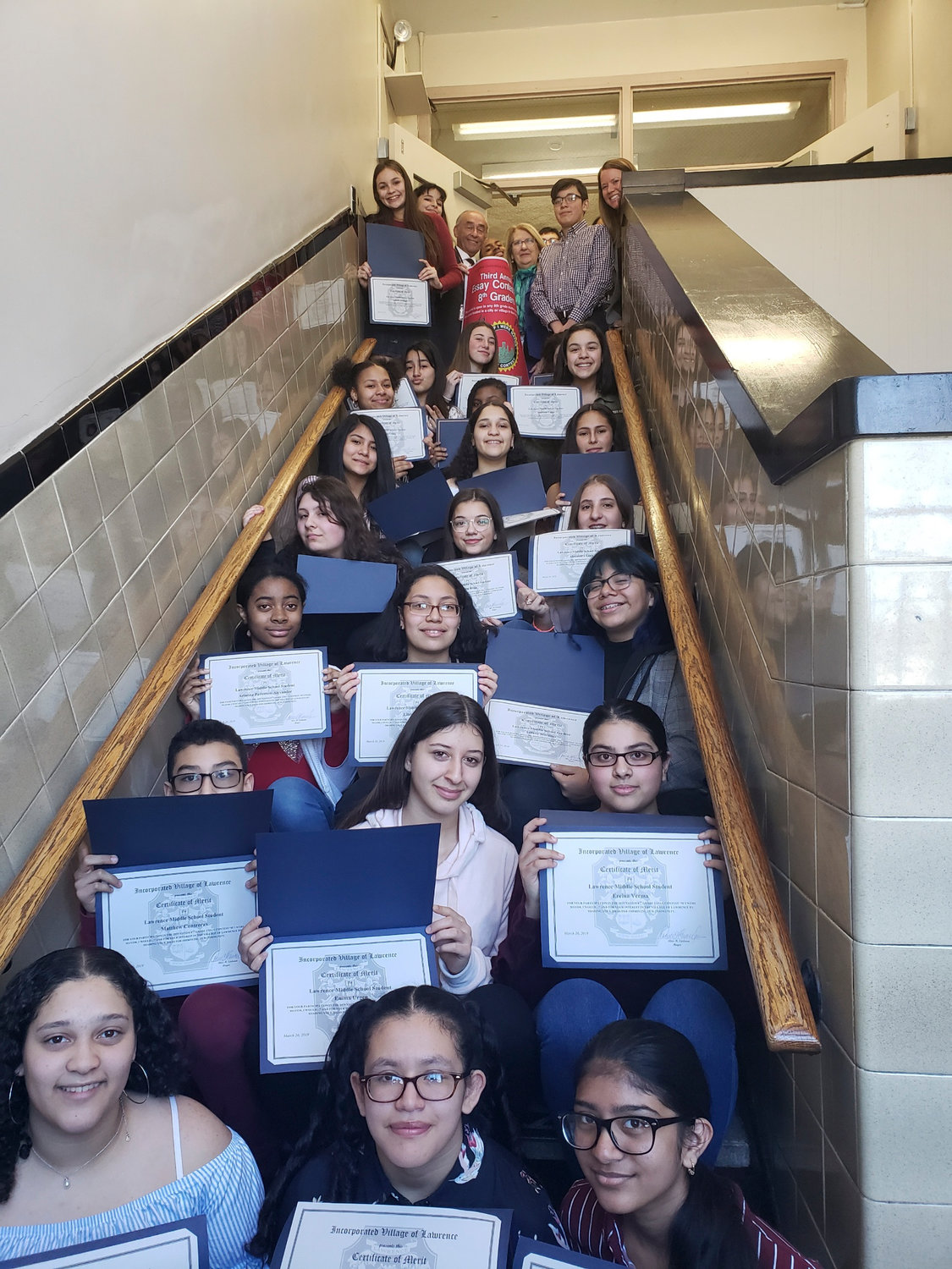 "Certificates of Merit were the coin of the realm for Lawrence Middle School students that wrote an essay, ""If I Were Mayor, I Would …"" At the top of the stairs were Lawrence village Mayor Alex Edelman, middle school Principal Willis Perry and Superintendent Dr. Ann Pedersen."