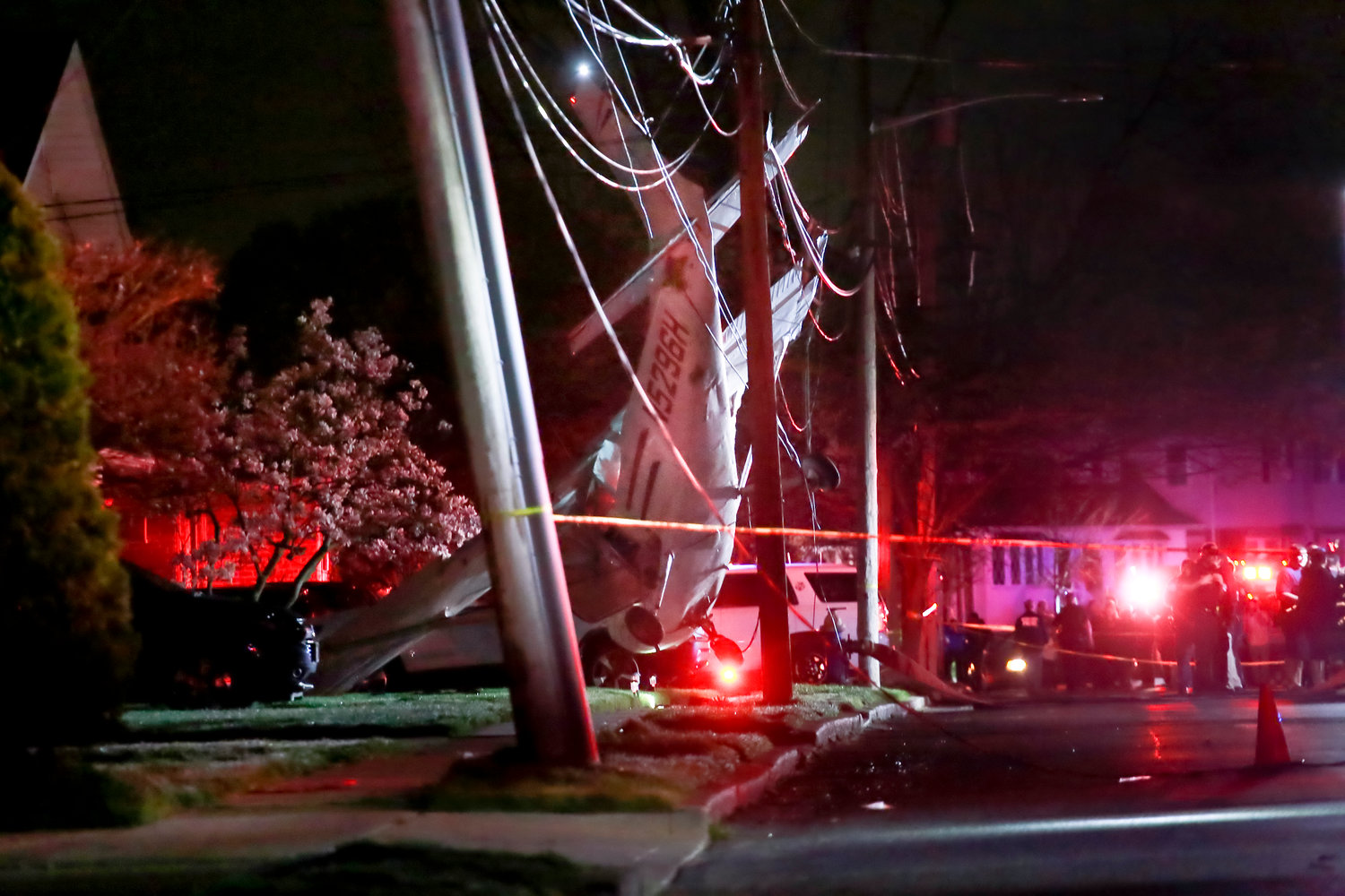 A single-engine prop plane was suspended a foot off the ground by power lines it crashed into in front of a Clarendon Drive home on Sunday. The pilot and passengers were unharmed.
