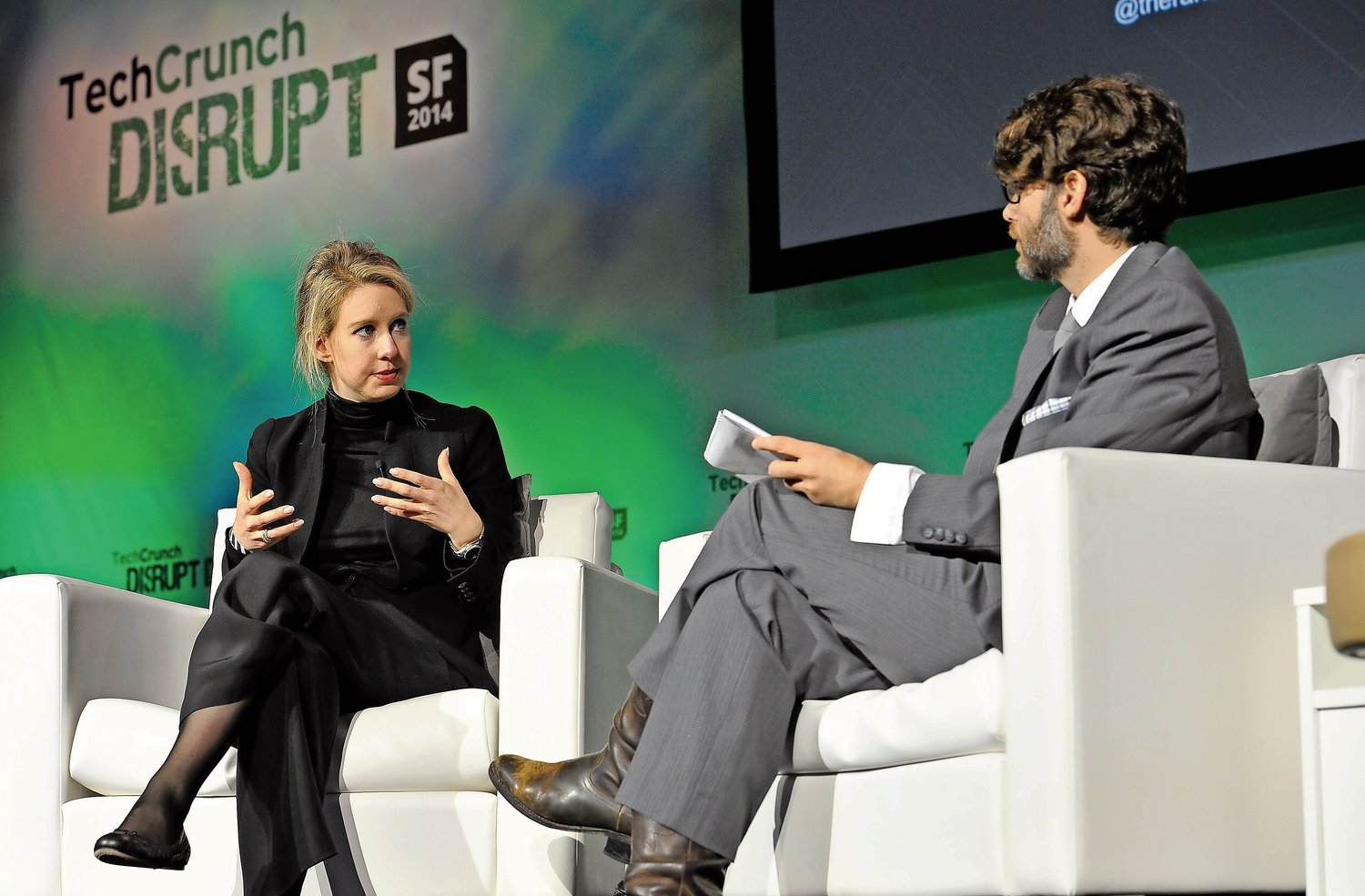 Kate Mckinnon will portray former Theranos Chairman and founder, Elizabeth Holmes, left, speaking at TechCrunch Disrupt tech conference in San Francisco, Calif. in 2014.