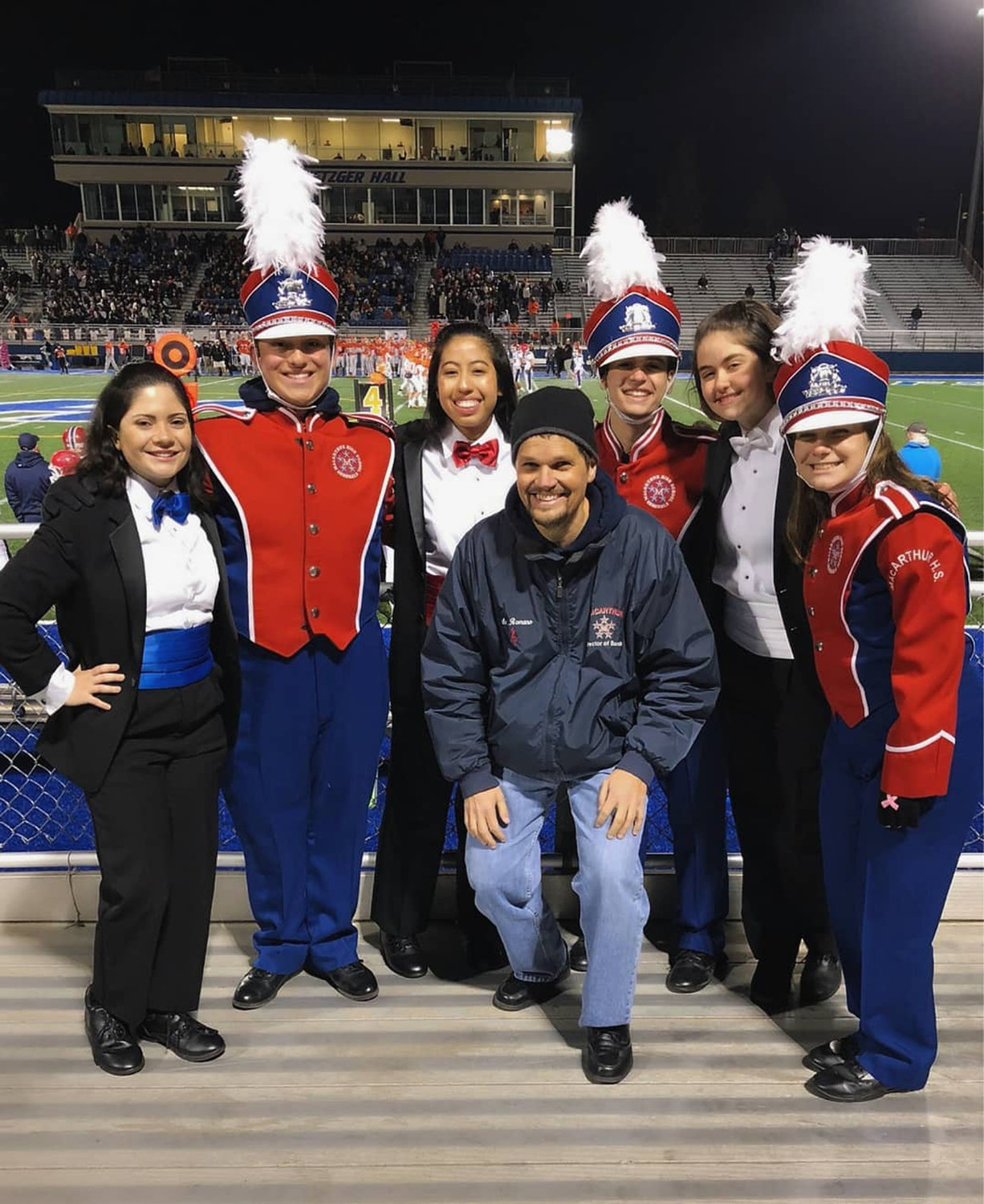"Kimberly Mestizo, WEARING red tie, with drum major colleagues, from left, Grace Derrick, Paul Giorlando, Joseph Novello, Briana Moss and Julia Gizzo at a performance of the MacArthur High School Band's ""Heavy Metal"" halftime show. Band director Joseph Romano is in front."