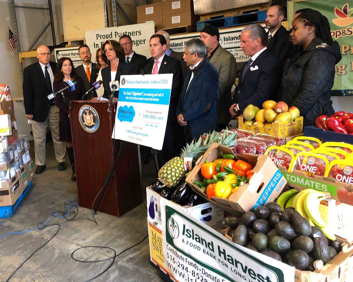 Island Harvest President Randi Shubin Dresner, at lectern, with State Sen. Todd Kaminsky to her right, was among the officials last Thursday to announce passage of a measure to reduce food in the waste stream by requiring large retailers to send unsellable but edible food to recovery organizations like Island Harvest.