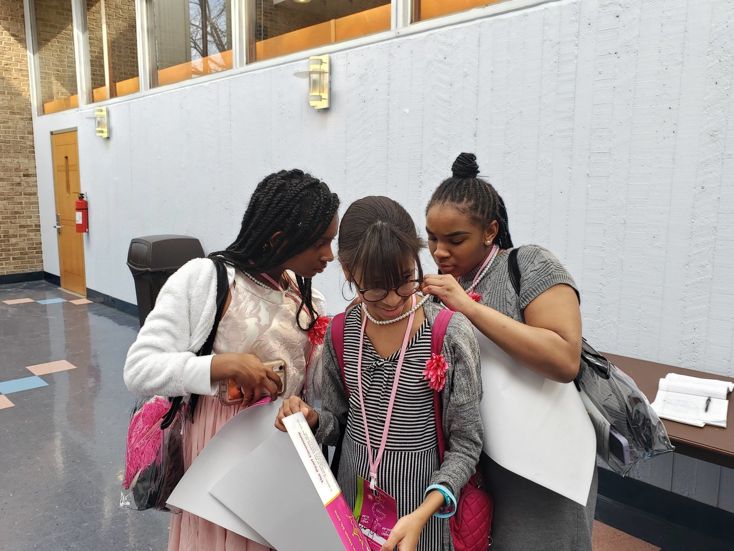 Shortly after receiving their pearl necklaces, Dodd seventh grader, Angela Morris, left and eighth grader Zun Eccleston, left, helped Nathalia Montero, center, fix the clasp of her necklace.