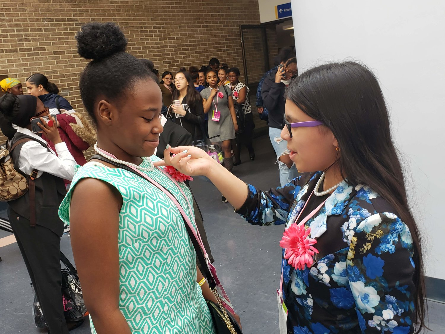 Dodd seventh grader Valeria Pizarro Torres, right, complimented eighth grader Willana Seree's pearl necklace after the closing ceremony of the Girlz Talk conference.