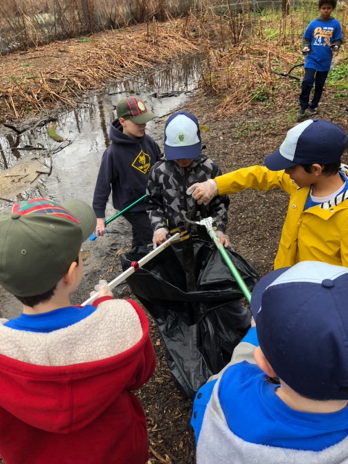 The cub scouts worked together to collect trash.
