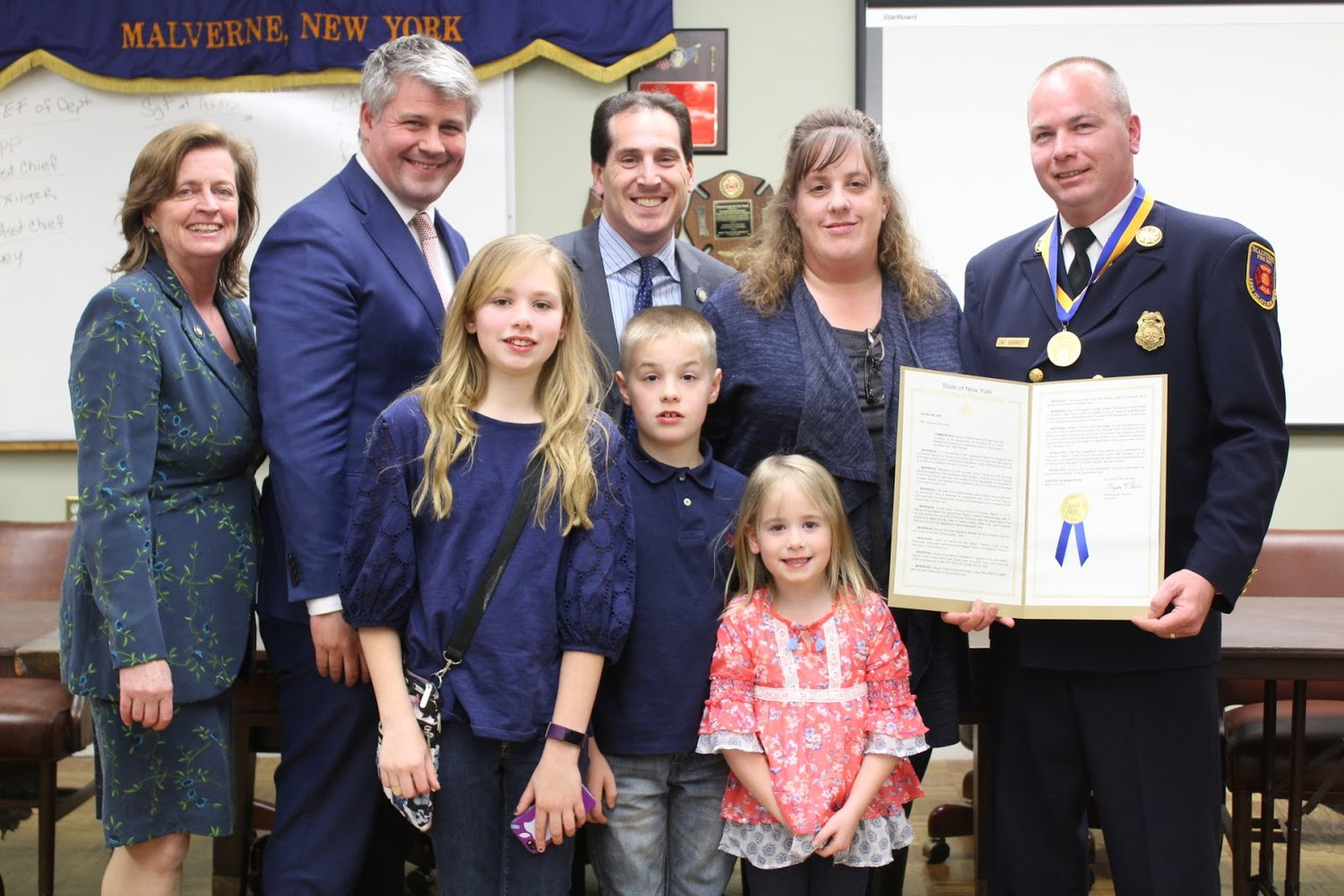 Malverne Fire Department Second Deputy Chief Ernest Bohringer, far right, with his wife, Sande; his children, Mackayla, Justin and Gabriella; along with State Sen. Todd Kaminsky, center, State Assemblywoman Judy Griffin, far left, and Malverne Mayor Keith Corbett.