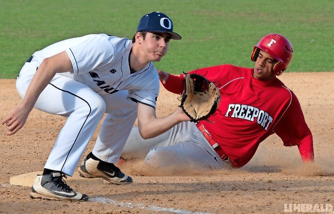 Freeport's Ronny Vicente slid safely into third base during the Red Devils' hard-fought series against Oceanside last week.