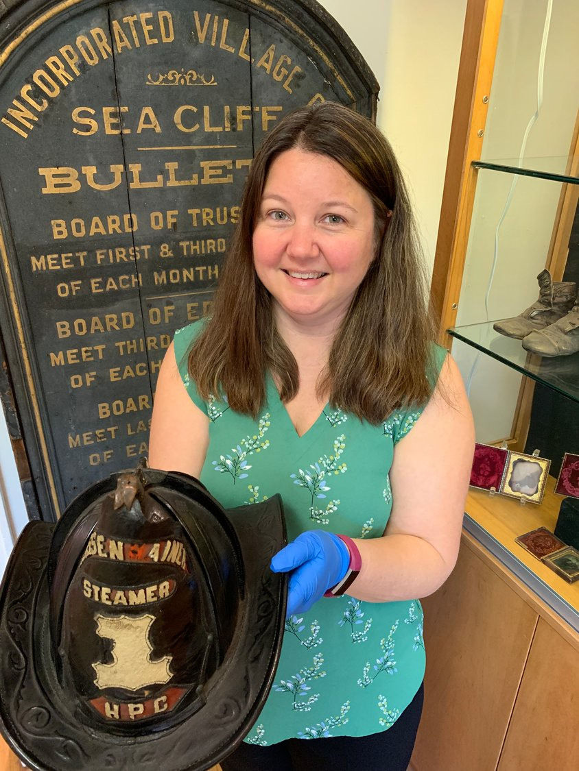Courtney Chambers, the museum's new executive director, with a firefighter's helmet from the original Geissenhainer Fire Company, a predecessor of the Sea Cliff Fire Department, which was organized in 1884.