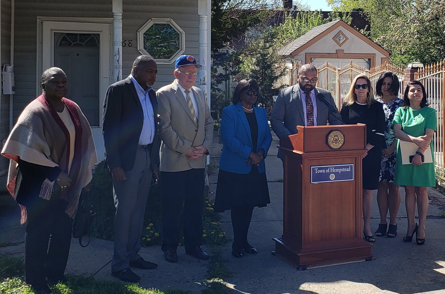 State Sens. Kevin Thomas, at lectern, Anna Kaplan, far right, and Town Supervisor Laura Gillen, third from right, held a news conference April 24 in front of a vacant home in Hempstead to address the area's shortage of affordable housing.
