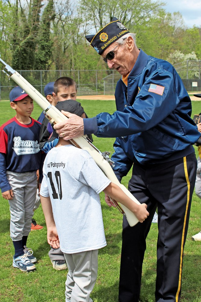 Legionnaire Carl Ring demonstrated to Lucas Pegion, 7, how to handle a rifle safely.