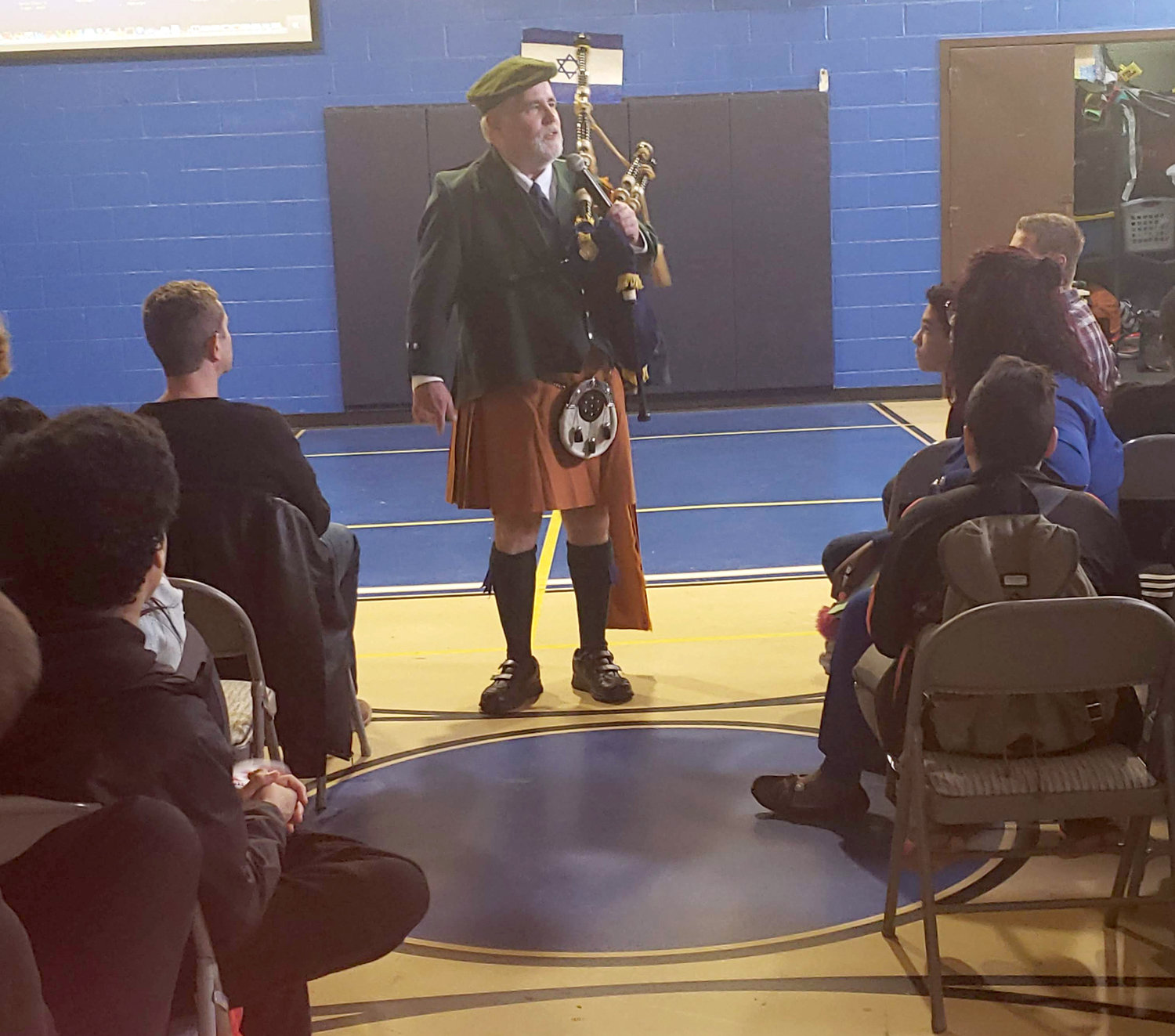 Kellenberg Memorial High School's music instructor, Robert Lynch explained the history of his kilt and sporran to the Woodward Children's Center students in between the songs he played on his bagpipe on April 30.