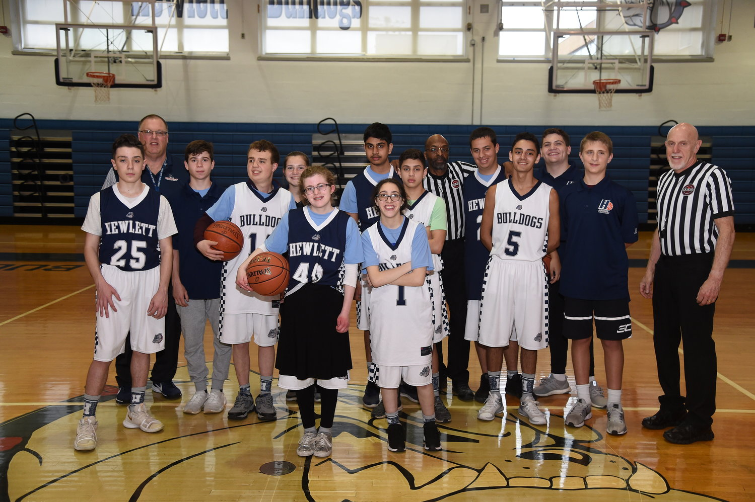 Hewlett High School's unified basketball team with coach Bill Dubin, far right in the back on May 6. The blue team is Bilaal Sadia (32), Jared Bostoff (21), Stephen Hoffman (25), Saif Kamal (24) and Shani Zlan (40). The white team is Matthew Dougherty (14), Ariana Siegel (1), Josh Tepper (5), Diego Gonzalez (13) and Daniel Gardener (3).