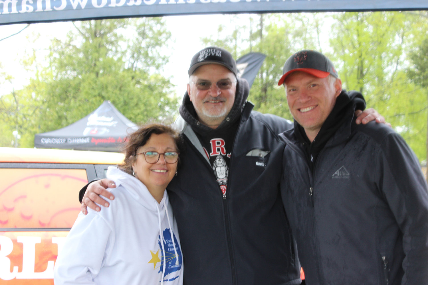 East Meadow Chamber of Commerce Vice President Christine Mooney, left, Chairman of the Board of Directors Frank Camarano and President Michael Levy set up shop at the finish line to greet runners and spectators.