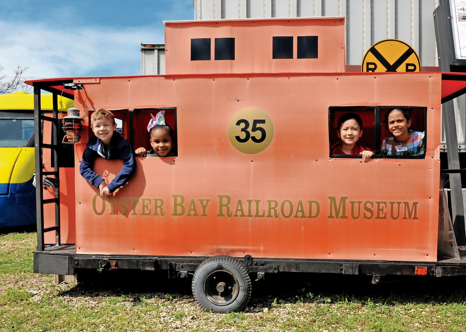 Trevor Malone, far left, Ana Bakalis, Austin Zhang and Olivia Adedano pretended they were passengers in a caboose at the Oyster Bay Railroad Museum's railyard.