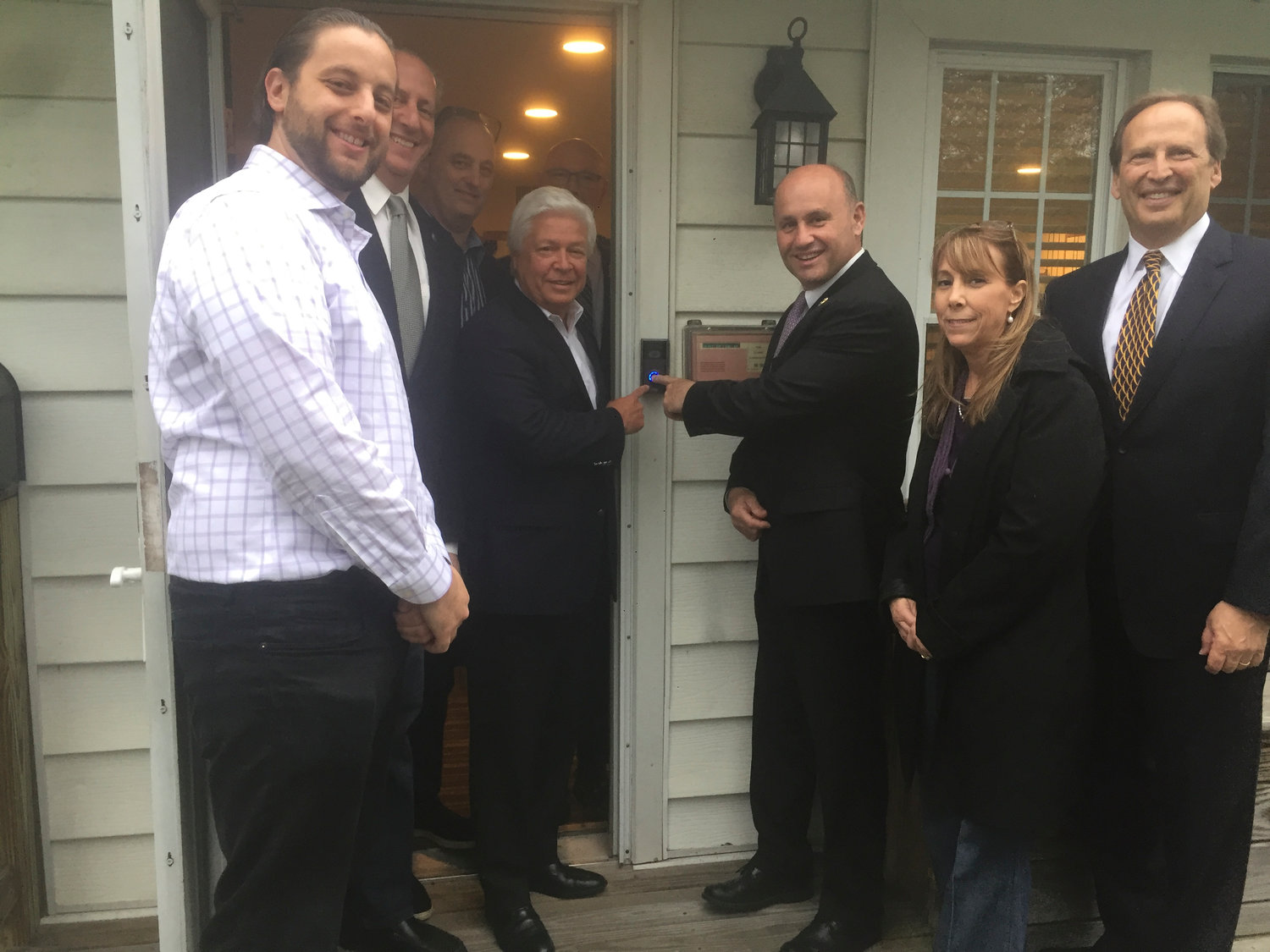 Hewlett Harbor Mayor Mark Weiss, center left, and Nassau County Police Commissioner Patrick Ryder pressed the button that activates the Ring Doorbell 2. With them were, from left, Hewlett Harbor resident Gil Bruh; Village Trustees Tom Cohen, Leonard Oppenheimer and Jonathan Polakoff; State Assemblyman Melissa Miller; and Trustee Kenneth Kornblau.