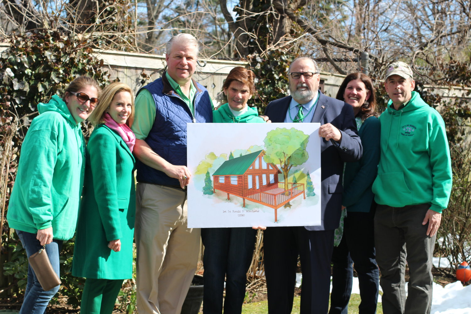 Kristine Winchester, far left, joined Town of Hempstead Supervisor Laura Gillen, Brian Rathjen, Marianna Winchester, Mayor Francis X. Murray, Deputy Mayor Kathleen Baxley and Michael Quilty at last year's St. Patrick's Parade. Winchester was presented with the rendering of a treehouse to be dedicated to her late son, Ronald, a Marine killed in Iraq in 2004.