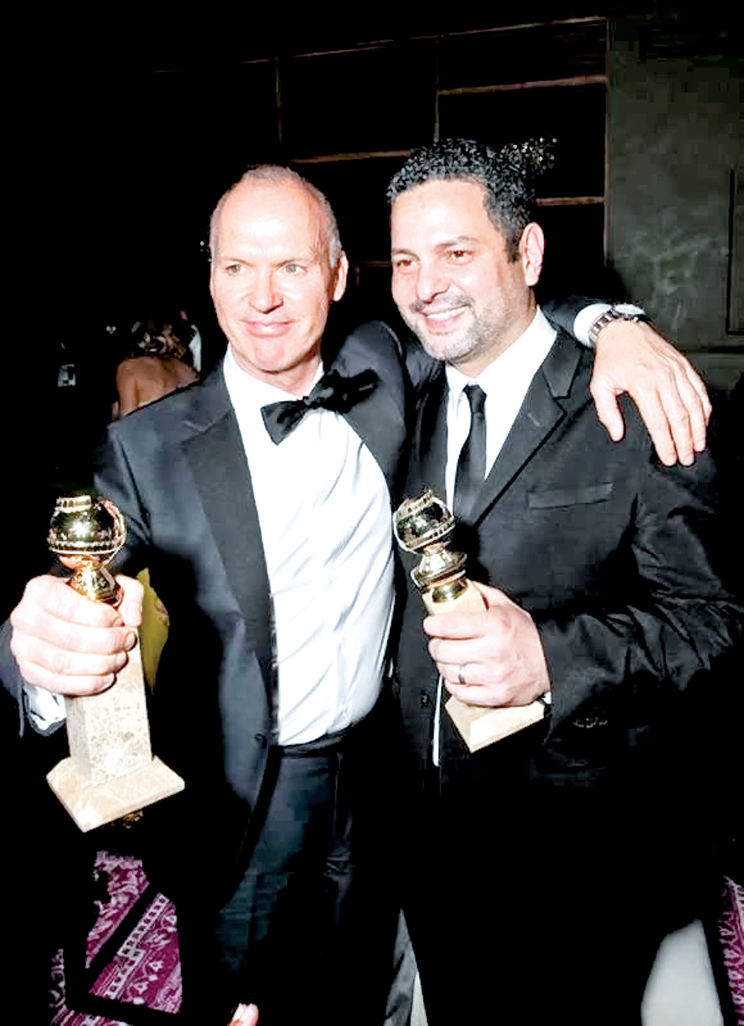 "Dinelaris, right, with ""Birdman"" star Michael Keaton in 2015 after they both won Golden Globes for their work on the film."
