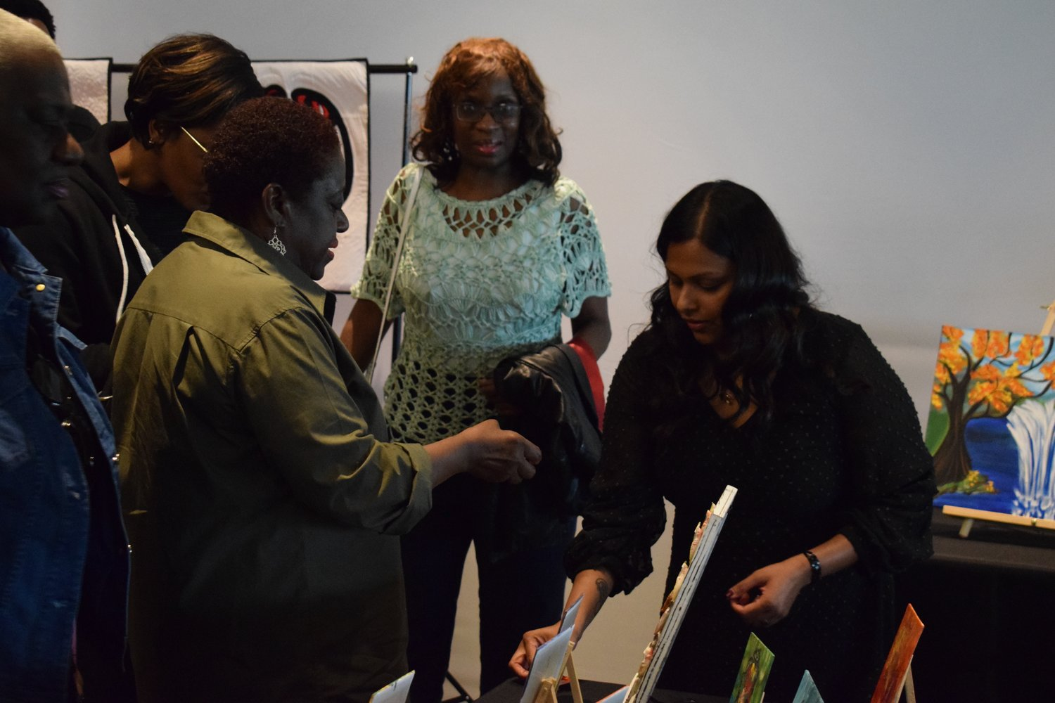 Elmont's Ann Robert, right, sold some of her artwork to residents at the Elmont Art Gallery on May 8.