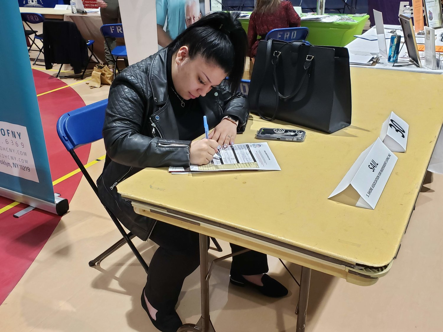 Nassau County Community College student, Kimberly Mejia, 19, from Hempstead, filled out a job application during the job fair at the Freeport Recreation Center on May 9.