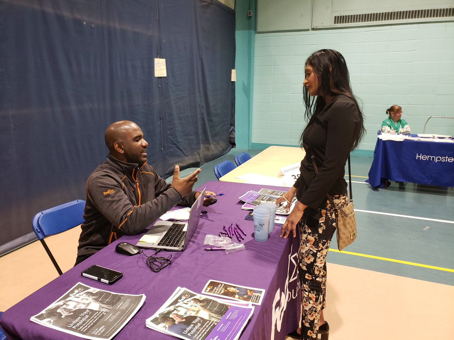 FedEx representative, Solomon Shearman, left, talked with Jennifer Jaikaran, a representative of Senator John Brooks' office during the annual job fair.